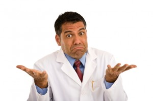 Puzzled male shrugging wearing lab coat
